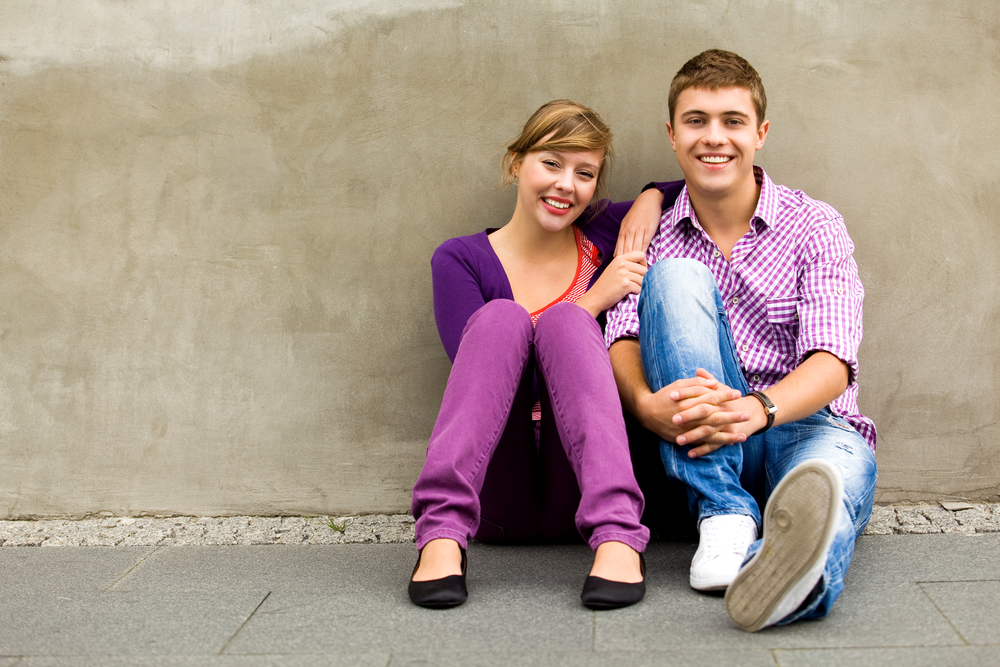 Teenager girl and boy sitting by wall