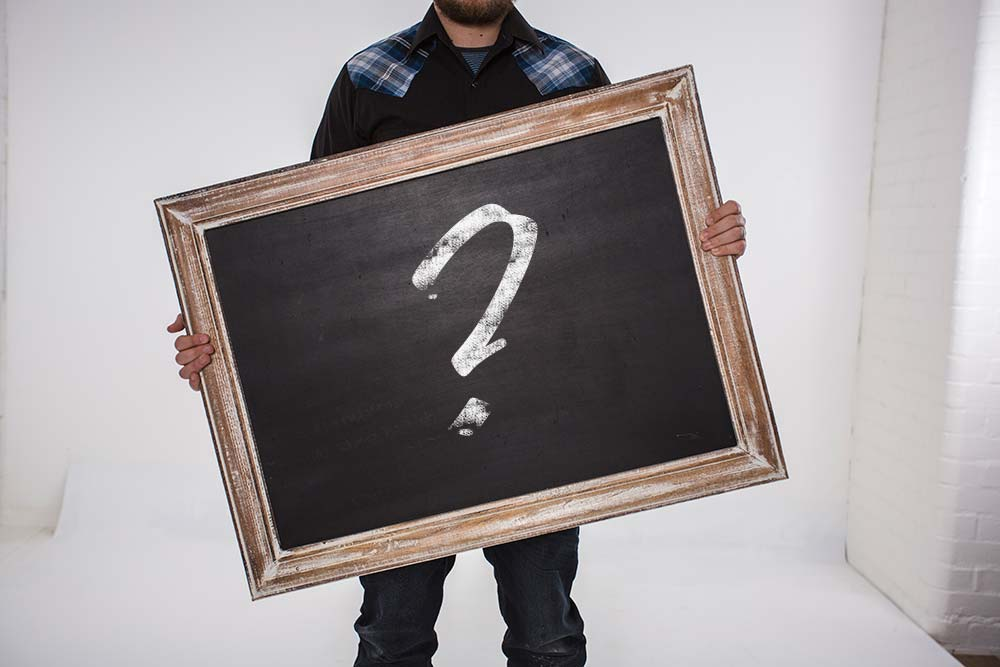 Man holding black board frame with chalk question mark