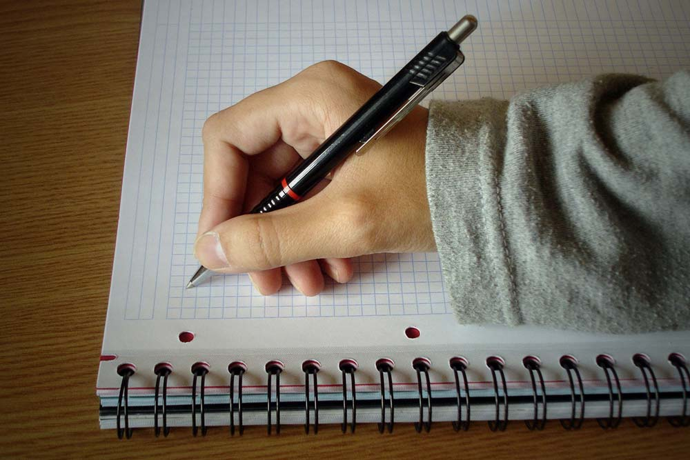 Hand with pen taking notes