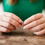 women's hands holding engagement ring