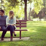 Couple on bench looking opposite ways