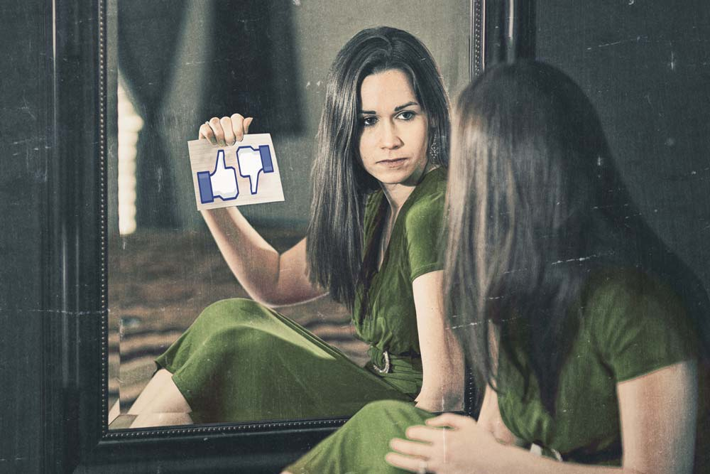 Woman looking into mirror. Reflection holding social like / dislike icons