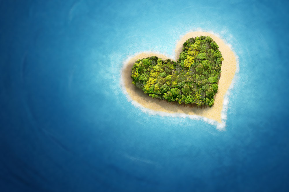 Heart shaped island with trees, bordered by small beach surrounded by deep blue sea.