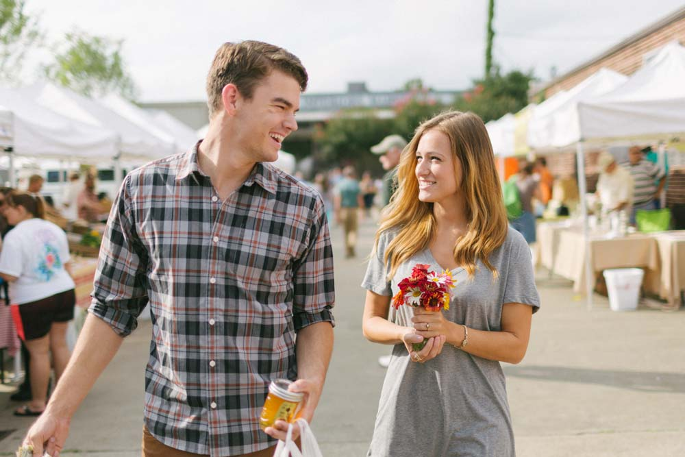 Young man and woman shopping happily at an open air market