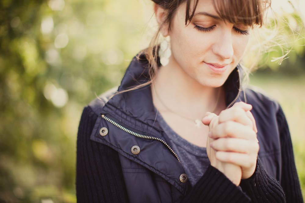 Young woman praying contentedly. Set against out of focus leafy background.