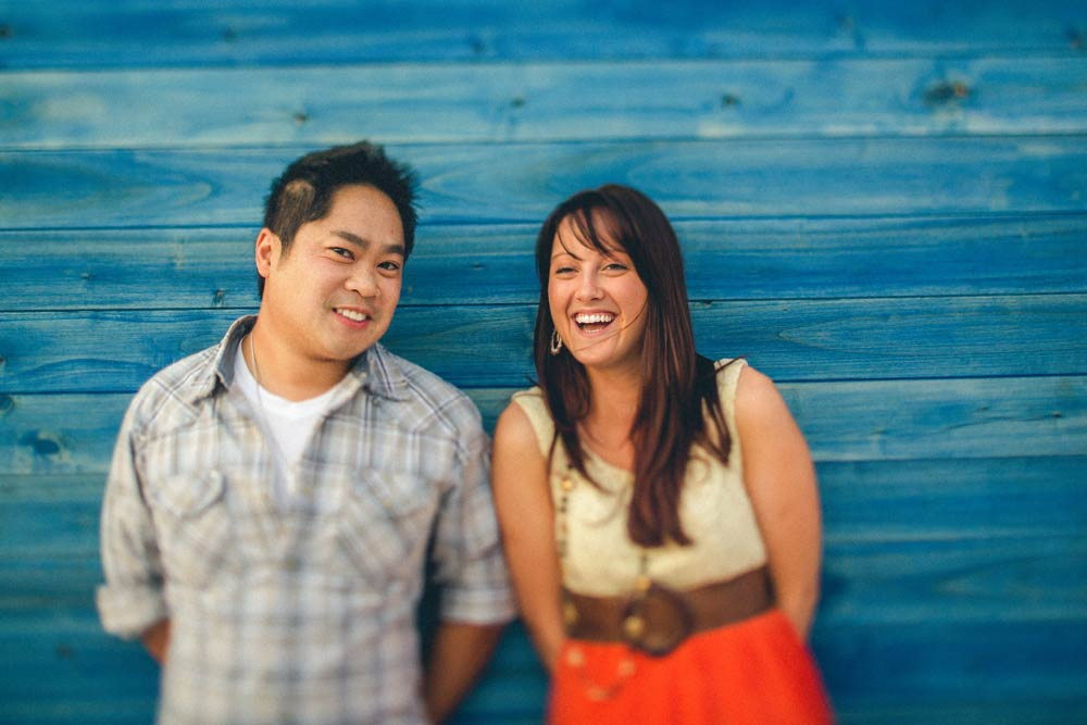 Young man and woman smiling and standing together with backs against a blue stained wooden slat wall