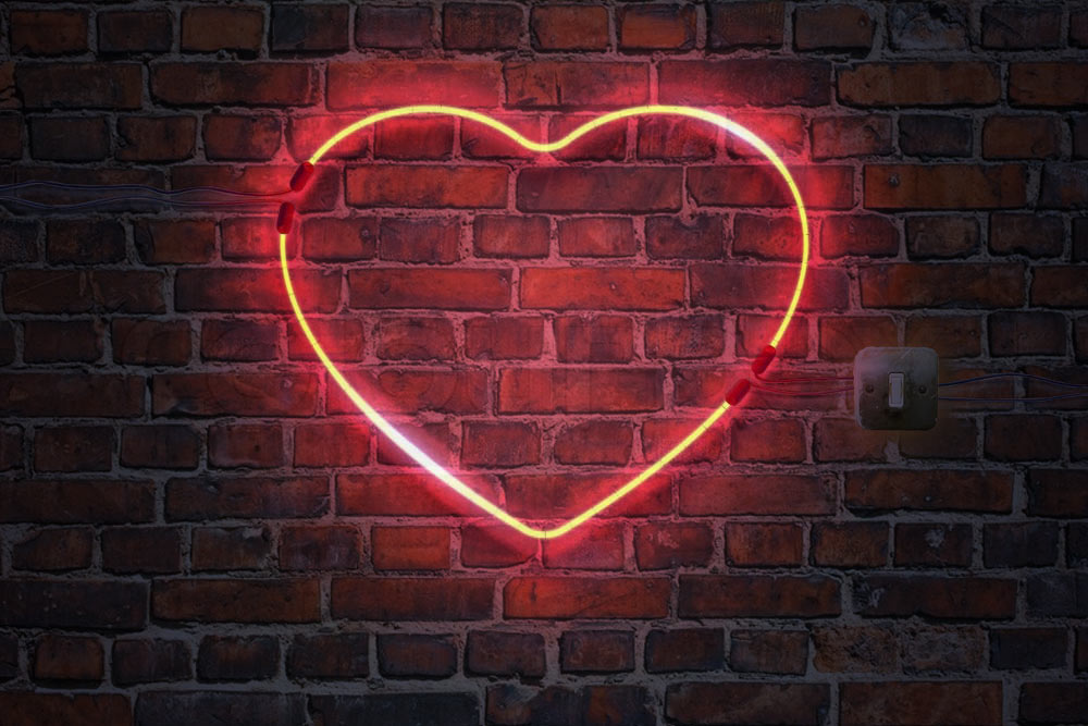 Red neon heart illuminating brick wall with wires and light switch