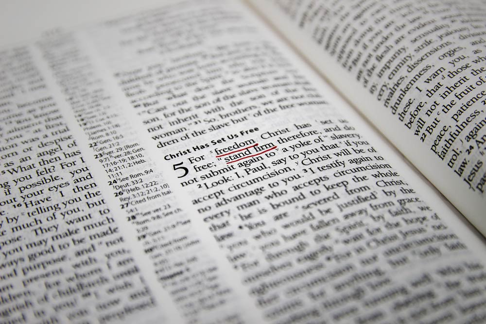 Close up of open Bible showing Galatians 5v1 with the words 'freedom' and 'stand firm' underlined in red