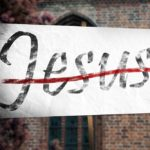 Placard held in front of a church with the word 'Jesus' struck through by a red line..