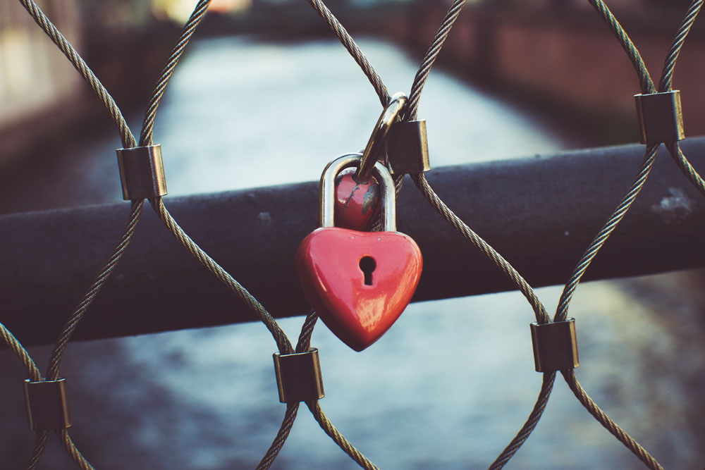 Close up of two red heart shaped padlocks locked together on a bridge railing