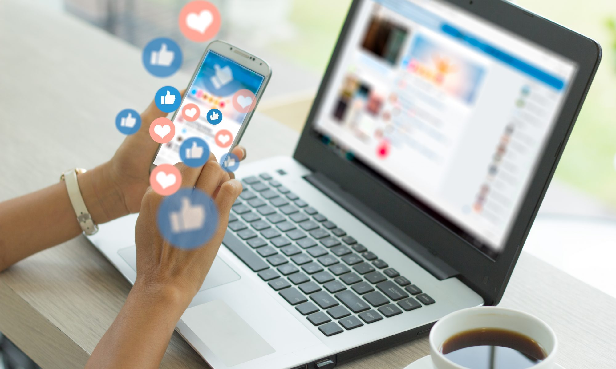 Woman's hand holding a phone with social media reactions floating above the screen, a laptop in the background showing social media